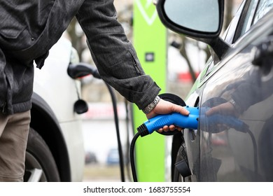 Male hand holding electrical socket while charging electrocar close-up