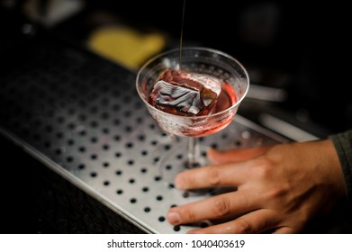 Male hand holding an elegant cocktail glass with sweet alcoholic drink with campari liquor and faceted ice on the bar counter