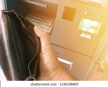 Male hand holding empty wallet infront of Auto teller machine