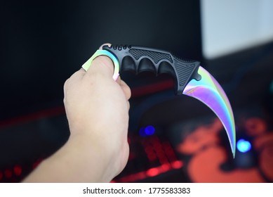 Male hand holding a faded karambit in a gaming background.