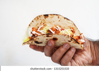 Male hand holding fish Tacos against white background, selective focus