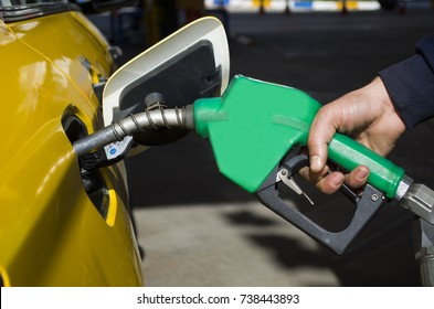 male hand holding gas pump one last drop of fossil fuel