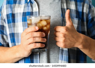 Male hand holding a glass with cola, close up