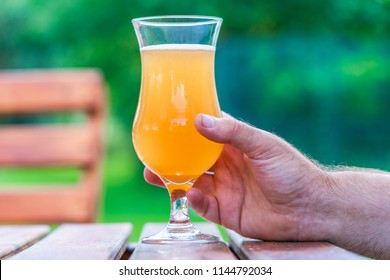 Male hand holding a glass of cold beer set on a table in the garden
