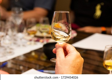 Male hand holding glass of white wine