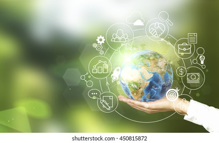 Male hand holding globe with abstract global business cycle sketch on green background. Elements of this image furnished by NASA