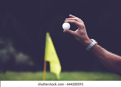 Male hand holding a golf ball with yellow hole flag on background, player holding golf ball with big copy space for your text message