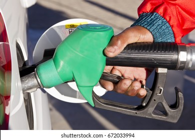 Male hand holding a green petrol or gasoline  pump while in a motor vehicle