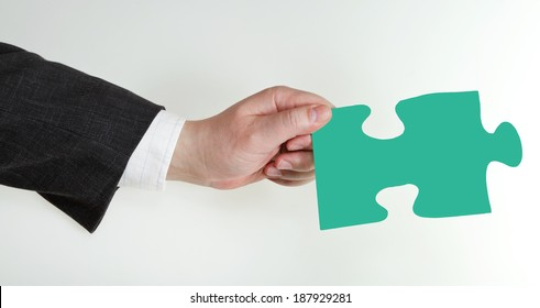 male hand holding green puzzle piece on grey background