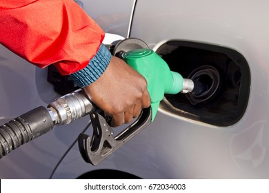 Male hand holding green unleaded petrol pump while filling the motor car