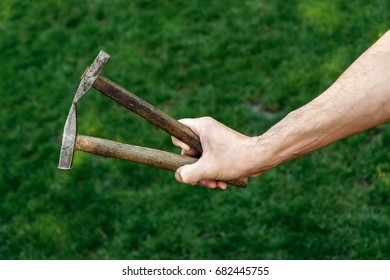 Male hand holding a hammer. Hammer in hand. Two hammers.
