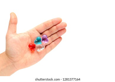 Male hand holding hearts of different colors. In the palm of the red, blue, white, lilac heart. Concept: uniting people. Peaceful coexistence of people on earth. Feast of St. Valentine. Copy space.