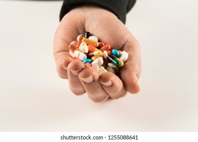 Male hand holding high number of  pills on white background. High resolution image for pharmaceutical industry.