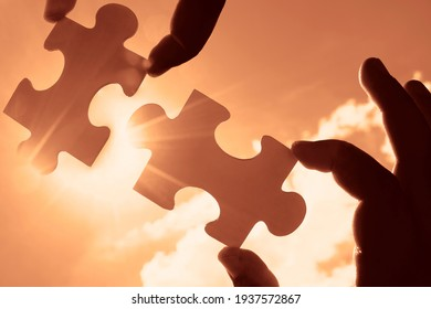 male Hand holding  jigsaw puzzle with  sunlight effect sky clouds. Strategies for business success. Collaboration and teamwork concept.