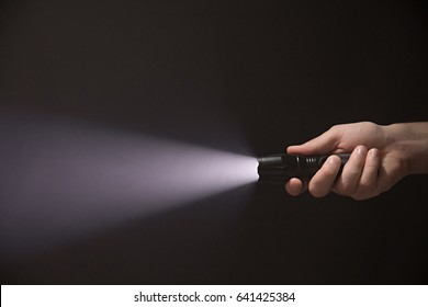 Male hand holding a led flashlight with a wide white beam on a black background, leaving the right side of the frame