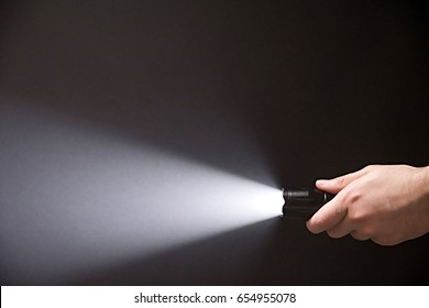 Male hand holding a led flashlight with white beam on a black background, leaving the right side of the frame