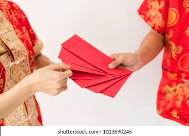 male hand holding many blank red envelopes with Angpao money while young girl with Chinese costume dress called qipao, choose one envelope. Chinese New year holiday on white background.