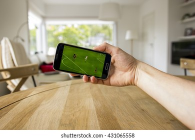 A male hand holding a mobile phone which displays a soccer match on the touch screen. An image on an interior background.