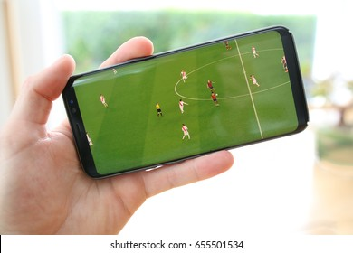 A male hand holding a mobile phone which displays a soccer match on the touch screen. The big green screen is in contrast with the overexposed background. An image on an interior background.