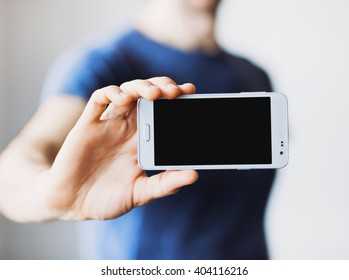 Male hand holding mobile smart phone with blank screen