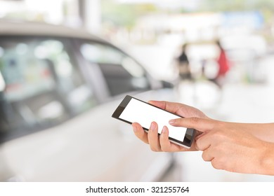 male hand is holding a modern touch screen phone and blur image of Commercially cars stand in show room of car shop.