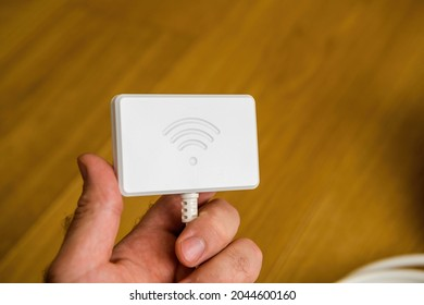 male hand holding new Wifi dongle for modern refrigerators - control with app and smartphone