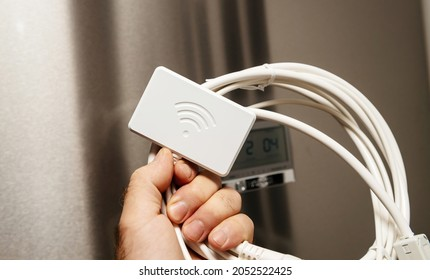 male hand holding new Wifi dongle for modern refrigerators with new fridge in background - control with app and smartphone