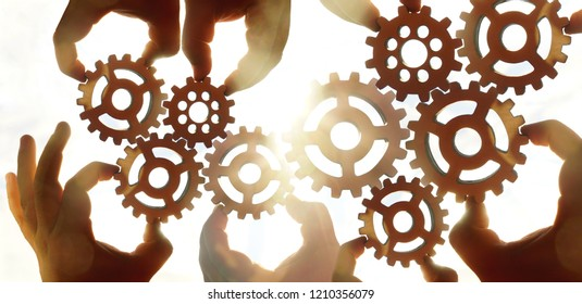 Male hand holding nine 9 wooden cog wheel, gear wheel on golden sky background. sunshine and yellow heaven.