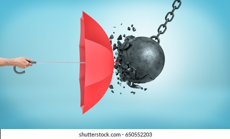 A male hand holding an open red umbrella which protects from a collision with a broken wrecking ball. Insurance and protection. Safety measures. IT defense.