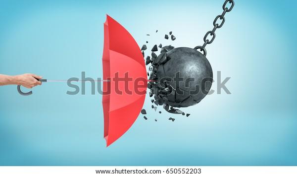 Мужская рука держит открытый красный зонтик, который защищает от столкновения с разбитым крушительным мячом. Страхование и защита. Меры безопасности. ИТ-защита.