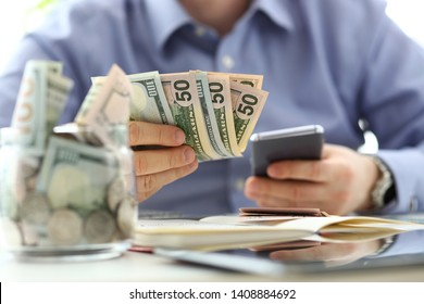 Male hand holding pack of banknotes and cellphone making some calculation planning his future expenses closeup concept