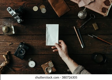Male hand holding paper note on vintage office desk. Flat lay