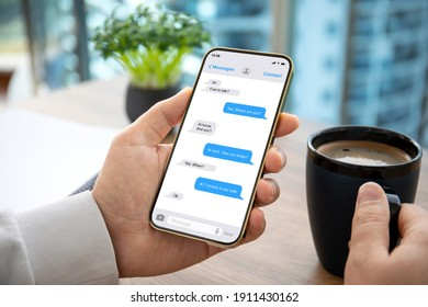 male hand holding phone with app messenger over table in office