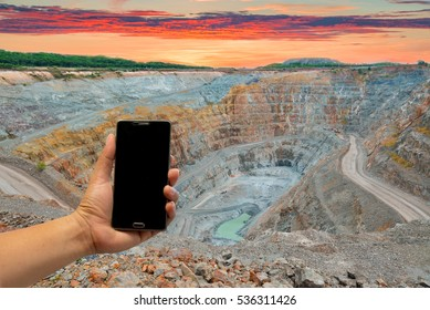 Male hand holding a phone with black screen The mine is located in Phichit Thailand. This area has been mined for copper, silver, gold, and other minerals