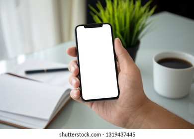 male hand holding phone with isolated screen above table in the office