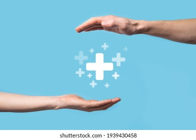 Male hand holding plus icon on blue background. Plus sign virtual means to offer positive thing (like benefits, personal development, social network)Profit,health insurance, growth concepts.