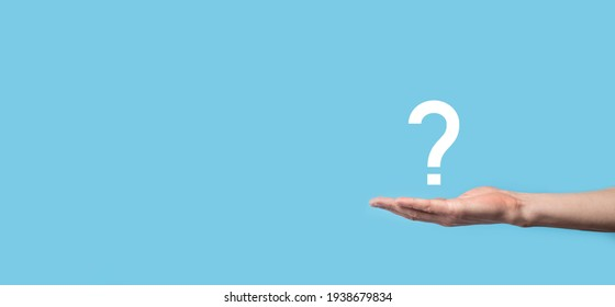 Male hand holding question mark icon on blue background.Banner with copy space. Place for text