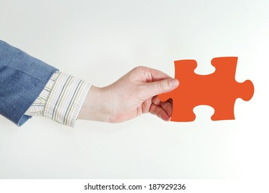 male hand holding red puzzle piece on grey background