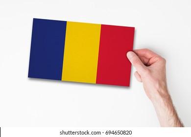Male hand holding romania flag