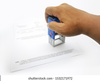 A male hand holding a self-inking, rubber company logo stamp. A paperwork. Office accessories.