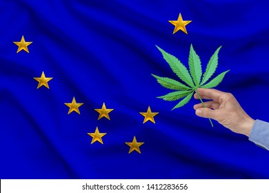 male hand holding a sheet of marijuana against the background of the silk national flag of the USA state of Alaska with folds, the concept of legalization of drugs