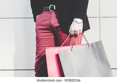 male hand holding a shopping bag, businessman hands holding bags, concept of purchasing and sales