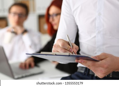 Male hand holding silver pen ready to make note in opened notebook sheet. Businessman in suit at workspace make thoughts records at personal organizer white collar conference signature concept