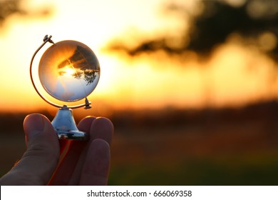 male hand holding small crystal globe in front of sunset. travel and global issues concept