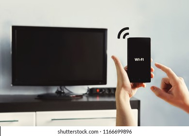 male hand holding a smartphone. Control your TV with smartphone. connectivity between smart tv and smart phone through wifi connection. to distribute the Internet through wifi from phone to computer
