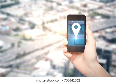 Male hand holding smartphone with location pin icon on blurry city background with copy space. Navigation concept