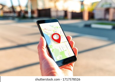 Male hand holding holding smartphone with online-a map on which the geolocation icon. In the background, a blurred street. Close up. Concept of online navigation and GPS