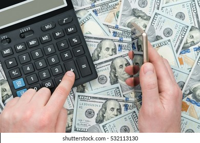 Male hand holding a smartphone and other presses a calculator button, which lies on the dollar background