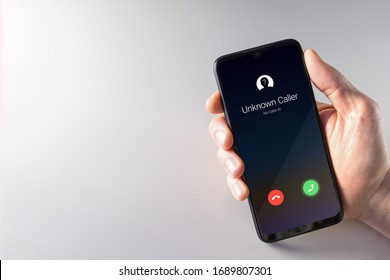 Male hand holding a smartphone with unknown caller displayed on screen. Privacy, fraud, cybercrime and spying concepts