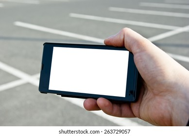 Male hand holding a smartphone with white screen at the parking lot or car park, close up.